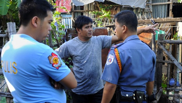 TRAGEDY IN CAVITE. Police officers talk to a relative of a victim following a shooting rampage in Kawit, about 40 kms (25 miles) south of Manila on January 4, 2013. AFP PHOTO / JAY DIRECTO