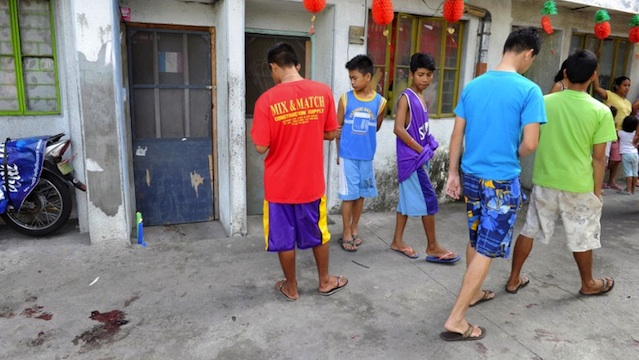 Residents walk past by a door with lighted candles (L) and blood stains (bottom L) after a gunman reportedly shot a mother and child during a rampage in Kawit, about 40 kms (25 miles) south of Manila on January 4, 2013. AFP PHOTO / JAY DIRECTO