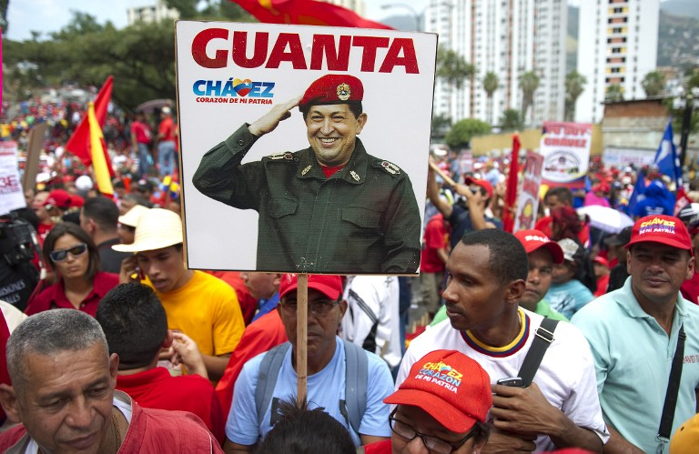 Supporters of Venezuelan President Hugo Chavez show a portrait of Venezuelan President Hugo Chavez in a rally to commemorate the 55th anniversary of the end of the dictatorship (1952-1958) of Marcos Perez Jimenez in Caracas on January 23, 2013. AFP PHOTO/JUAN BARRETO