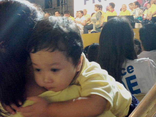 OUR FUTURE. A child rests on his mother's shoulder while Team PNOY candidates promise to make his future bright.