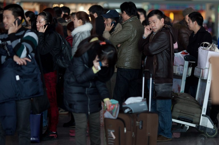GOING HOME. Lunar New Year travelers queue at Beijing's international airport on February 6, 2013. AFP PHOTO / Ed Jones