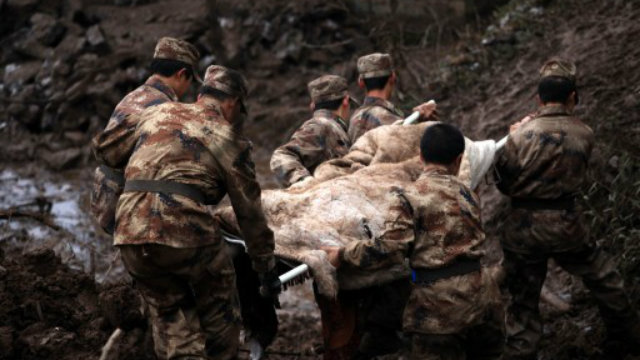 LANDSLIDE. Chinese rescue workers carry a dead body they found while searching for buried residents in a disaster-hit area in Gaopo village, southwest China's Yunnan province on January 11, 2013. Photo by AFP.