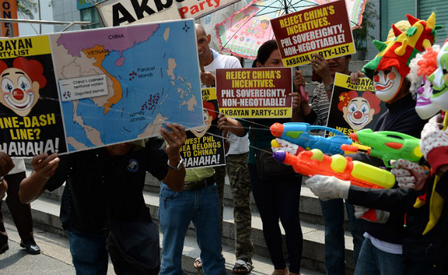 'REJECT CHINA'S INCENTIVES.' Activists dressed as clowns and holding water pistols spray a map illustrating China's claim to the South China Sea during a protest in front of the Chinese consular office in Makati on March 3, 2014. Photo by Ted Aljibe/AFP