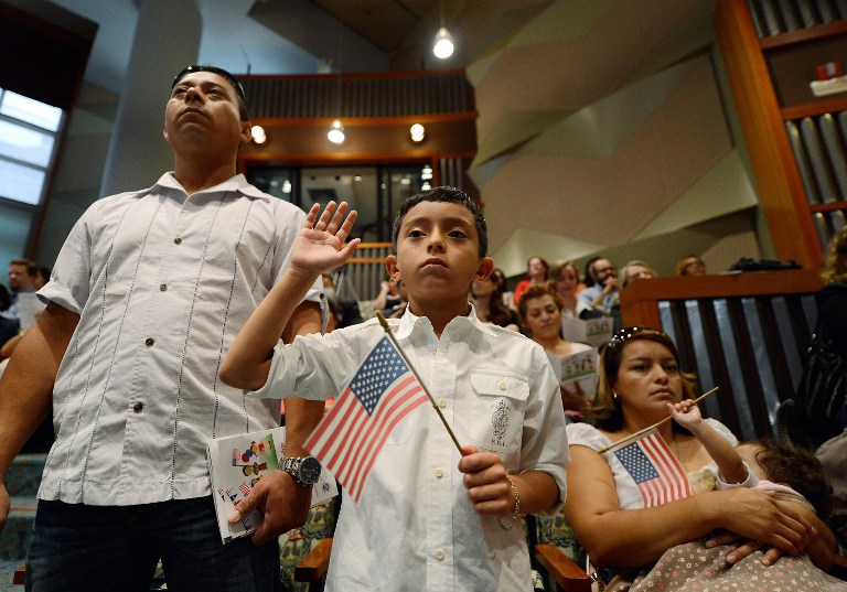 U.S. citizenship candidate Ricardo Barrera, 8, takes the oath of citizenship as his father Ricardo Barrera (L), mother Reina Barrera and his sister Ashley, 1, look on during a naturalization ceremony at the Los Angeles Central Library on September 19, 2012 in Los Angeles, California. Kevork Djansezian/Getty Images/AFP