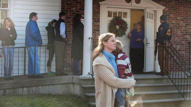 SCHOOL SHOOTING. A woman holds a child as people line up to enter the Newtown Methodist Church near the the scene of an elementary school shooting on Friday in Newtown, Connecticut. Photo by Douglas Healey/Getty Images/AFP