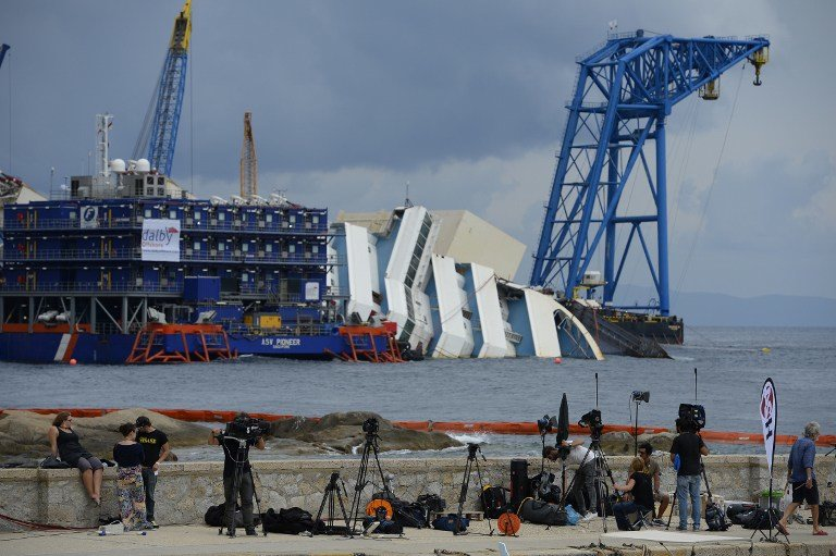 shows journalists working with the wreck of Italy's Costa Concordia