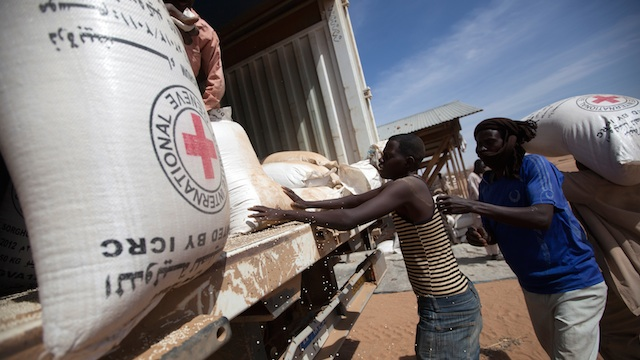 FOOD AID. In this photo, community members at the Nifasha IDP camp in North Darfur unload bags of sorghum from a WFP truck, 11 February 2014, in Shangil Tobaya, Sudan. Albert González Farran/UN Photo