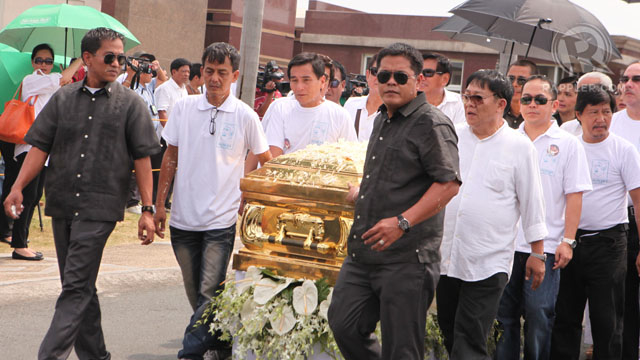 TO THE BURIAL SITE. Pall bearers -- among them, Manila Mayor Alfredo Lim -- carry it a short distance from inside a chapel to the burial grounds. Photo by Geric Cruz
