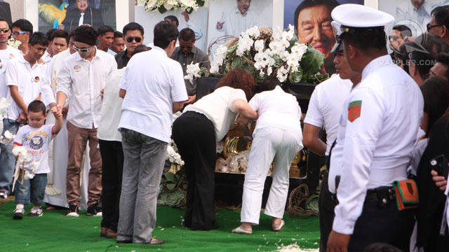 FLOWERS. Family and closest friends throw flowers into Dolphy's tomb before it is sealed. Photo by Geric Cruz