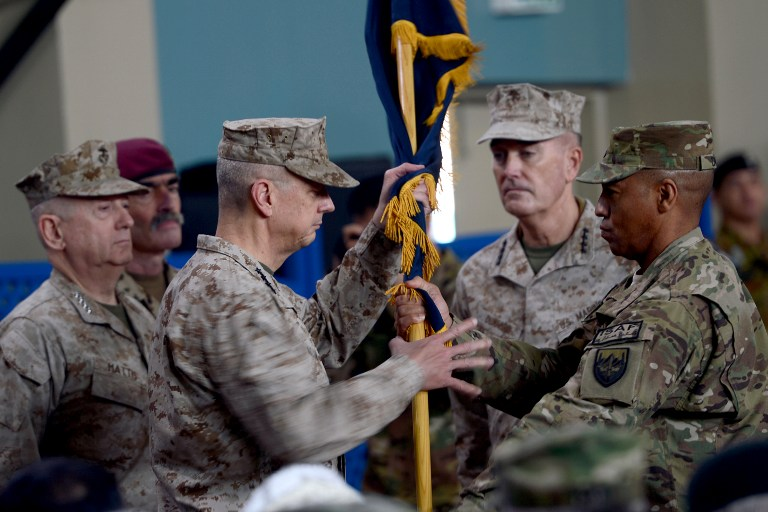 TURN OVER. Former NATO commander US General John Allen (3rd L) hands over a flag to US General Joseph F. Dunford (2nd R) as he takes over as commander of NATO in Afghanistan at the ISAF headquarters in Kabul on February 10, 2013. Massoud Hossaini/AFP