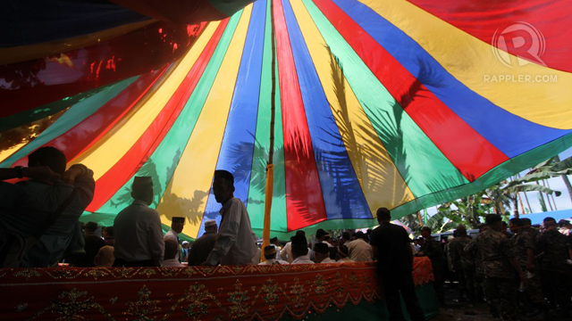 FESTIVE MOOD. Colorful buntings, flags and tents as well as the ebullient music from the kulintang mark the Bangsamoro assembly in one of the most heavily armed camps of the MILF. Photo taken by Karlos Manlupig