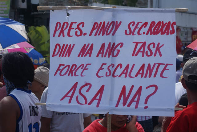 Rally participants display placards calling on President Aquino to immediately act on extrajudicial killings in Escalante. Photo by Gilbert Bayoran