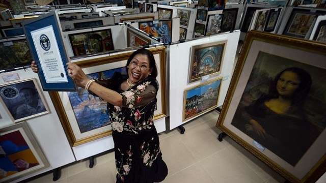 WORLD RECORD. Georgina Gil Lacuna holds up her world record certificate for having the largest collection of jigsaw puzzles. Photo from AFP