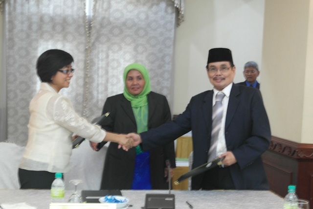 'BIG CHANCE.' Government chief negotiator Miriam Coronel-Ferrer (L) shake hands with Moro Islamic Liberation Front chief negotiator Mohagher Iqbal (R) during the the closing of the 39th round of talks. Looking on is Che Kashna, head of the Malaysian secretariat. Photo by OPAPP