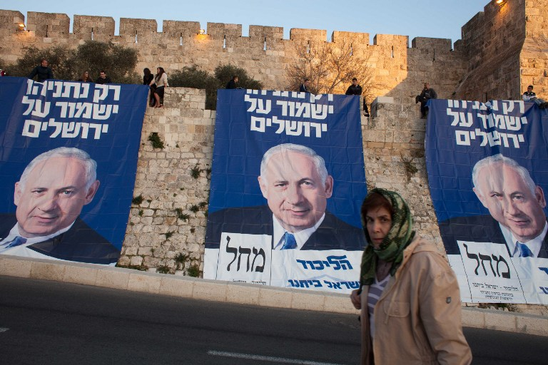 A woman walks in front of campaign posters of Israeli Prime Minister and Likud party leader Benjamin Netanyahu, with text reading in Hebrew: &quot; Only Netanyahu will guard Jerusalem&quot; along the walls of the old city of Jerusalem on January 20, 2013, ahead of the Israeli general election on January 22. AFP/ EMIL SALMAN