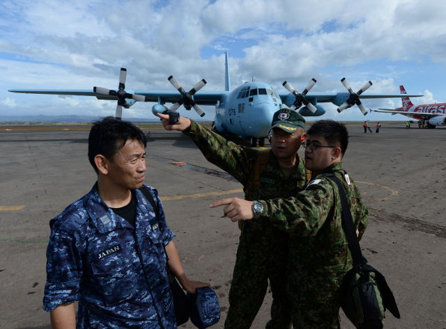 JAPANESE AID. Japanese military beside their Japanese Air Force C130 cargo plane after its arrival at Tacloban Airport on November 20, 2013. Mark Ralston/AFP Photo