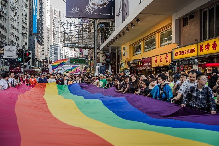 Participants carry a large flag as they take part in a Gay Pride procession in Hong Kong on November 10, 2012. AFP PHOTO / Philippe Lopez