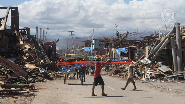 DEVASTATION. A man carries construction supplies across a road in the middle of Cateel, Davao Oriental, in the aftermath of typhoon Pablo (Bopha), December 10, 2012. Photo by Karlos Manlupig.