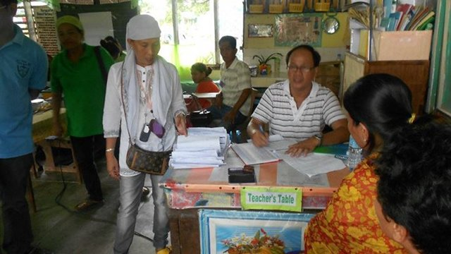 REGISTRATION. An election officer assists registrants in a school in Maguindanao. Photo from LENTE