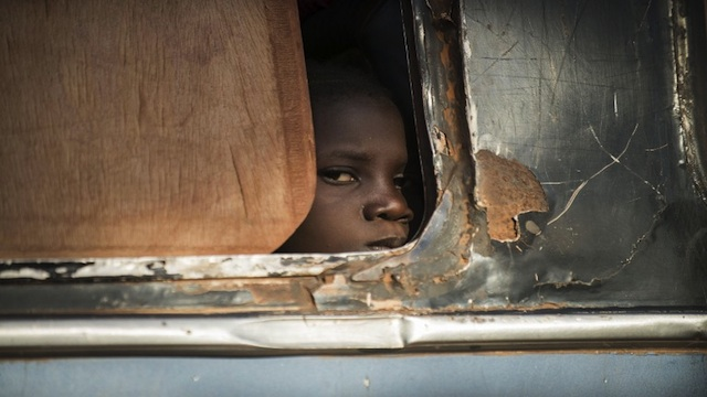 CHECKPOINT. A Malian girl looks out from a bus as Malian army soldiers prepare to check the vehicle and passengers at a checkpoint in the city of Niono, on Jan 18, 2013. AFP photo