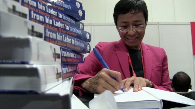 AUTHOR. Ressa signs the inner jacket of her new book at a security conference in Singapore. Photo by Rappler/Katherine Visconti.