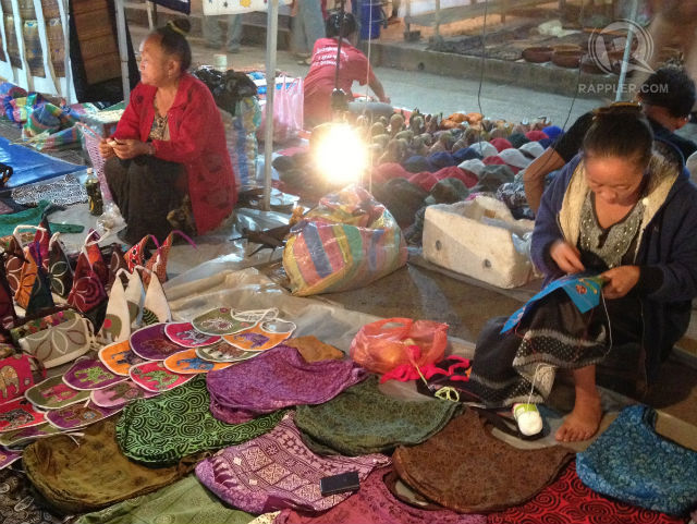 NIGHT MARKET. Hmong and other tribal people set up a nightly market to sell traditional and contemporary textiles and other souvenirs in Luang Prabang