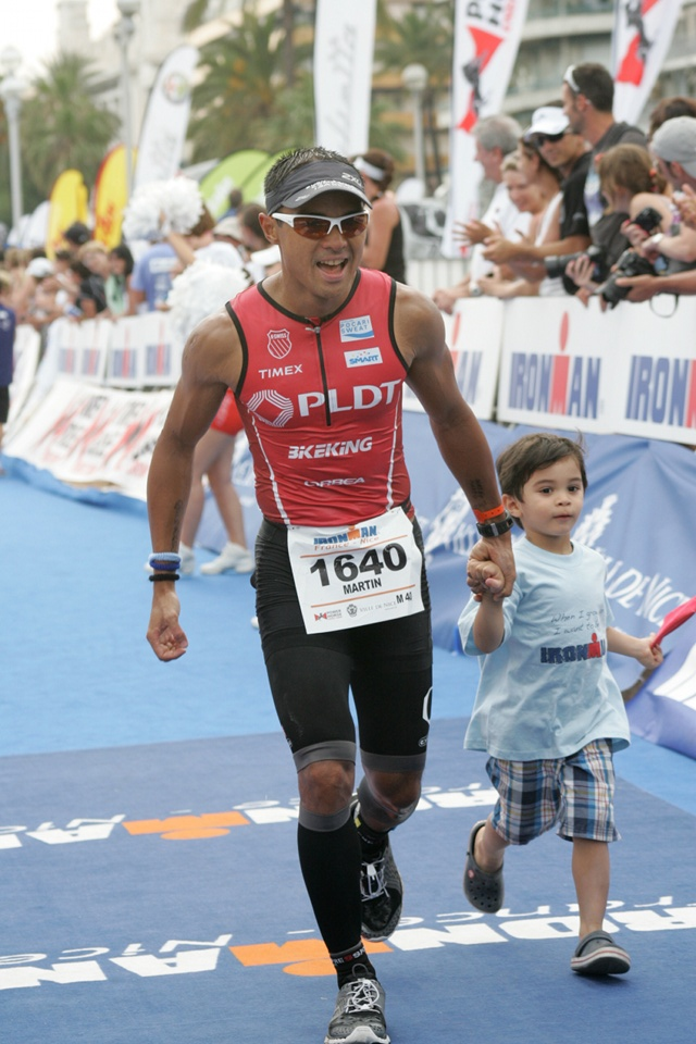 FINISHING STRONG. Martin Lorenzo holds his son Matteo's hand as he crosses the finish line of the Ironman race. Photo from Martin Lorenzo.