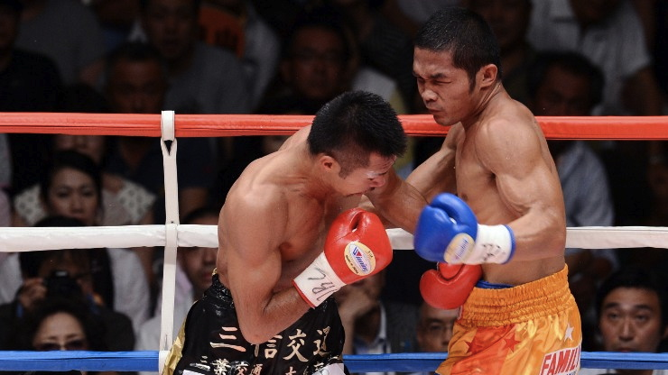 UPSET. Michael Fareñas (R) exchange punches with WBC super featherweight champion Takashi Uchiyama. File photo by AFP/Toshifumi Kitamura