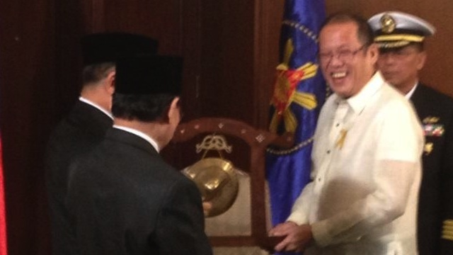 In this photo tweeted by Deputy Presidential Spokesperson Abigail Valte, President Benigno Aquino III (R) smiles as he receives the Gong for Peace from Moro Islamic Liberation Front (MILF) chief Murad Ebrahim (L, partly hidden) during their meeting at Malacañang Palace, October 15, 2012.