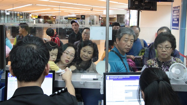 NO STAMP. Chinese visitors line up at immigration booths at Ninoy Aquino International Airport in Manila. Photo by Jedwin Llobrera