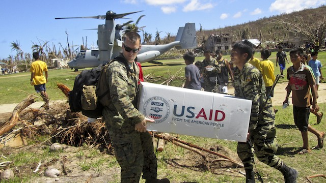 FROM THE AMERICAN PEOPLE. U.S. Marine Capt. Joseph White (L) and Philippine army Pfc. Vic D. Victorlano (R) carry USAID relief supplies from an MV-22 Osprey in Basey, Samar, Philippines, Nov. 18, 2013. Photo by the US Department of Defense/US Marine Corps Capt. Caleb Eames