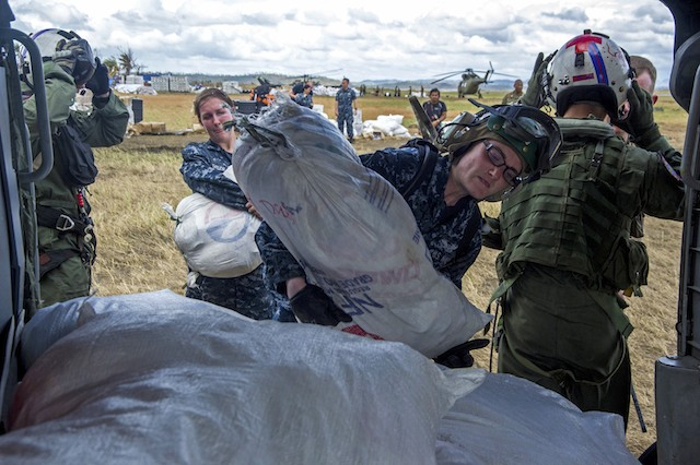 AID DELIVERY. U.S. Navy Petty Officer 3rd Class Deanna Coutts (C) loads a bag of supplies onto an MH-60S Seahawk helicopter to be airlifted to nearby villages in support of Operation Damayan in Tacloban, Philippines, Nov. 20, 2013. U.S. Navy photo by Petty Officer 2nd Class Trevor Welsh