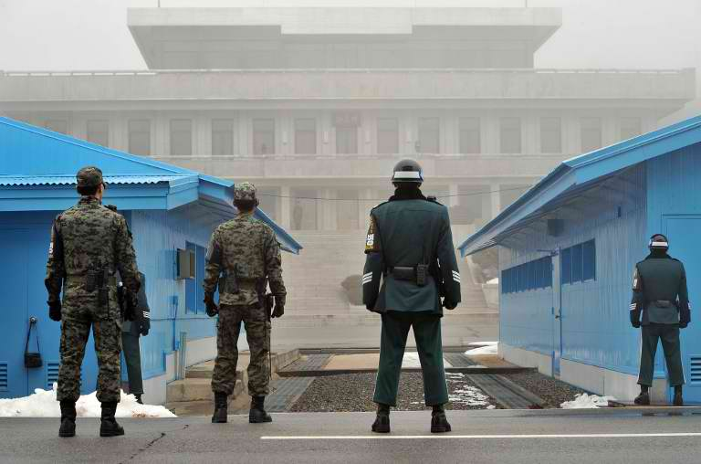 TRUCE IN DANGER? South Korean soldiers stand guard in fog as a North Korean soldier (C far) is seen at the truce village of Panmunjom in the demilitarized zone dividing North and South Korea on February 27, 2013. AFP PHOTO / JUNG YEON-JE
