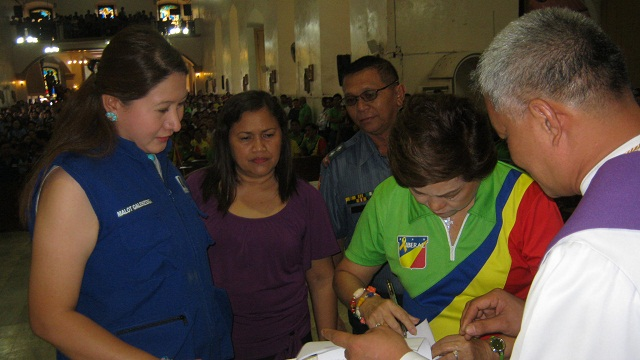 PLEDGE OF PEACE. Incumbent mayor Carmen L. Cari signs peace covenant while Marilou V. Galenzoga watches and waits for her turn.
