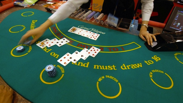 GAMBLING PARADISE. A dealer plays card with visitors during a two-day exhibit on the gaming industry in Manila, 22 March 2007. AFP PHOTO/ROMEO GACAD