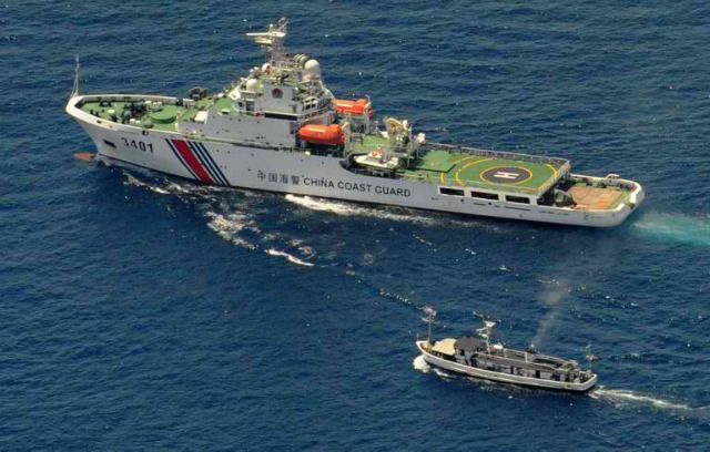 DAVID VS GOLIATH. A Chinese coast guard ship (top) and a Philippine supply boat engage in a standoff as the Philippine boat attempts to reach Ayungin Shoal, a reef claimed by both countries, on March 29, 2014. Photo by Jay Directo/AFP