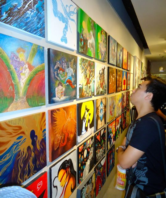 ART APPRECIATION. A comic book fan marvels at the Pinoy comics-inspired artwork