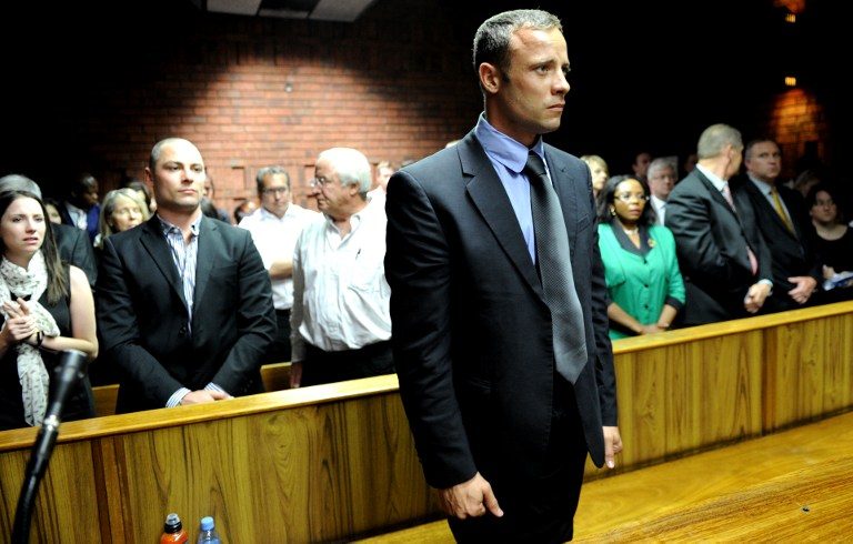South African Olympic sprinter Oscar Pistorius (C) appears on February 19, 2013 at the Magistrate Court in Pretoria as he father Henke (3rd L), brother Carl (2nd L) and sister Aimee (L) attend. AFP PHOTO / STEPHANE DE SAKUTIN