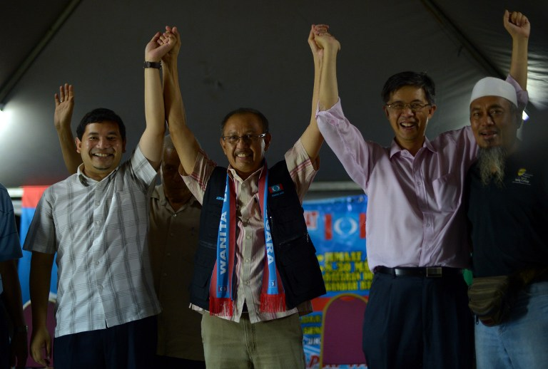 This picture taken on February 15, 2013 shows Rafizi Ramli (L), the strategist for the polical party of opposition leader Anwar Ibrahim, joining hands with other political leaders at a late night corner meeting in Kuala Lumpur. AFP PHOTO / SAEED KHAN