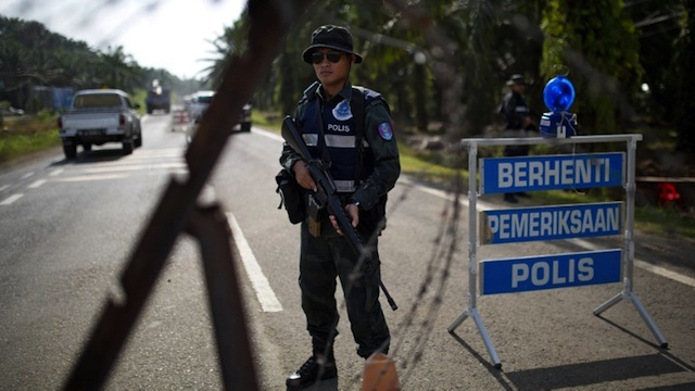LOCKDOWN IN SABAH. An armed Malaysian policemen mans a security checkpoint in Lahad Datu on March 6, 2013. AFP PHOTO / MOHD RASFAN