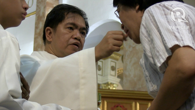 COMMUNION. Monsignor Rolando Dela Cruz gives communion during the Simbang Gabi mass on Sunday, December 16, 2012. Photo by Katherine Visconti.