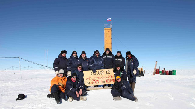 "A handout photo provided by the Russia's Arctic and Antarctic Research Institute taken at the Vostok station in Antarctica on February 5, 2012, shows Russian researchers posing for a picture after reaching the subglacial lake Vostok. The scientists hold the sign reading: ""05.02.12, Vostok station, boreshaft 5gr, lake at depth 3769.3 metres."" AFP PHOTO / ARCTIC AND ANTARCTIC RESEARCH INSTITUTE PRESS SERVICE"
