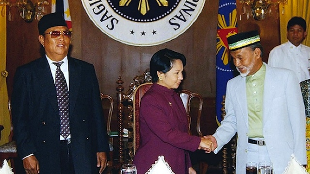 HEIR TO THE THRONE. President Gloria Macapagal-Arroyo (C) shakes hands with Sultan Esmail Kiram (R) while Sultan Jamalul Kiram III looks on at left during a meeting in Malacaang on September 18, 2002. AFP PHOTO/MALACANANG PALACE