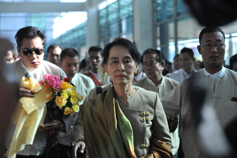 Myanmar opposition leader Aung San Suu Kyi (C) arrives at Yangon International Airport before departing on an overseas trip to Hawaii and South Korea on January 24, 2013. AFP PHOTO / Ye Aung THU