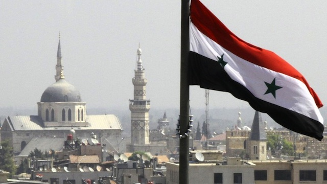 RAGING WAR. The Syrian flag flutters above Damascus on September 20, 2012. AFP PHOTO/LOUAI BESHARA