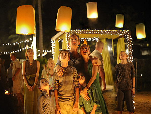 LIGHT BEFORE DARK. Oaklee Pendergast, Tom Holland, Ewan McGregor, Naomi Watts, and Samuel Joslin (foreground center, from left) at the calm before the storm
