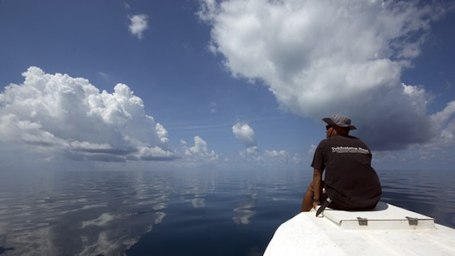 PATROLLING THE REEF. A park ranger looks out for possible intruding vessels on a patrol boat. Photo from TRNP website