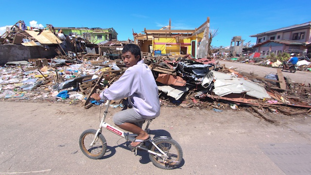 OBLITERATED TOWN. A resident rides his ramshackle bike through the debris in Cateel. Photo by Karlos Manlupig