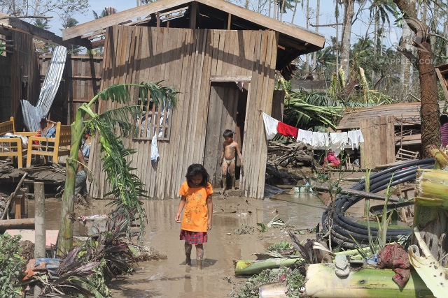 Children infront of their damaged home in New Bataan, Compostela Valley, December 5, 2012. Photo by Karlos Manlupig.