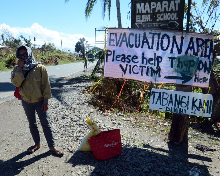 """TABANGI KAMI DINHI."" A resident stands next to a sign near a school serving as an evacuation center for victims of Typhoon Pablo (Bopha) in the town of Maparat in Compostela Valley province on December 8, 2012. AFP PHOTO / TED ALJIBE"